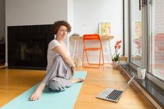 Vrouw die yoga met online app op computer in haar woonkamer doen stock foto's