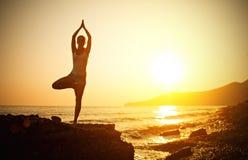 Vrouw die yoga op het strand doen bij zonsondergang Stock Foto