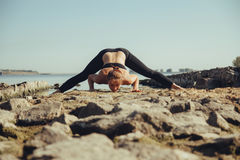 Vrouw die yoga op het strand doet Royalty-vrije Stock Foto's