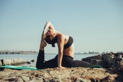 Vrouw die yoga op het strand doet Royalty-vrije Stock Afbeeldingen