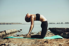 Vrouw die yoga op het strand doet Royalty-vrije Stock Foto