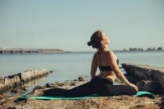 Vrouw die yoga op het strand doet Royalty-vrije Stock Afbeelding