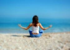 Vrouw die yoga op het strand doet Stock Foto