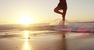 Vrouw die yoga op het strand doet stock footage