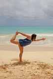 Vrouw die yoga op strand doet Stock Afbeeldingen