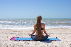 Vrouw die yoga op strand in halve lotusbloem doet Stock Foto's