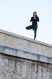 Vrouw die yoga in stad doen Stock Fotografie