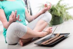 Vrouw die yoga thuis doet Stock Afbeelding
