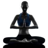 Vrouw die yoga uitoefenen die aangesloten bij zittingshanden mediteren Stock Fotografie