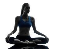 Vrouw die yoga uitoefenen die silhouet mediteren Stock Fotografie