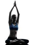Vrouw die yoga uitoefenen die zittingshanden bij aangesloten silhouet mediteren Royalty-vrije Stock Foto's