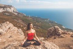Vrouw die yogaasana in bergenlandschap doen stock afbeeldingen