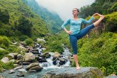Vrouw die yogaasana doen in openlucht bij waterval Stock Fotografie