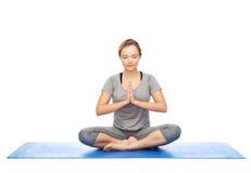 Vrouw die yogameditatie in lotusbloem maken op mat stellen Royalty-vrije Stock Afbeelding
