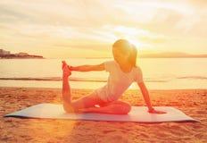 Vrouw die yogaoefening doen bij zonsondergang Stock Foto