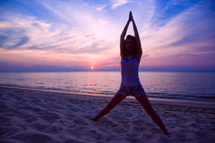 Vrouw die yogaoefening op het strand doet Stock Foto
