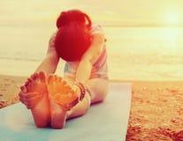 vrouw die yogaoefening op strand doet
