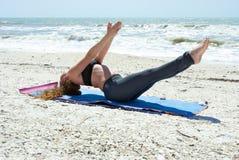 Vrouw die yogaoefening op strand in vissen doet Royalty-vrije Stock Fotografie