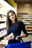 Vrouw die yoghurt in supermarkt kiest Stock Foto