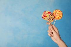 Vrouw die yummy suikergoed op kleurenachtergrond houden royalty-vrije stock afbeeldingen