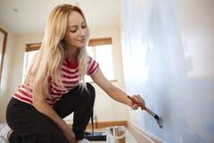 Vrouw die Zaal in Nieuwe Huis het Schilderen Muur met Borstel verfraaien stock foto's