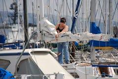 Vrouw die zeilboot voorbereidt Stock Foto's