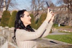 Vrouw die zelf-portret in openlucht nemen Royalty-vrije Stock Afbeeldingen