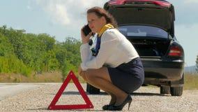 Vrouw die zenuwachtig op de telefoon naast een gebroken auto spreken stock footage