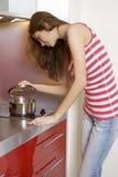 Vrouw die zich bij de keuken bevindt Stock Fotografie