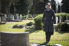 Vrouw die zich bij graf bevinden stock foto's