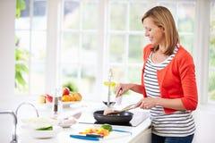 Vrouw die zich bij Haardplaat bevinden die Maaltijd in Keuken voorbereiden Royalty-vrije Stock Foto's