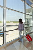 Vrouw die zich bij het luchthavenvenster bevinden. Royalty-vrije Stock Afbeelding