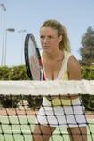 Vrouw die zich bij Netto Tennis bevindt royalty-vrije stock afbeeldingen