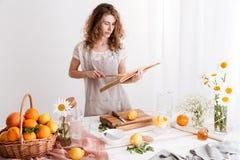 Vrouw die zich binnen dichtbij lijst met heel wat citrusvruchten bevinden Royalty-vrije Stock Fotografie
