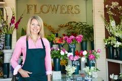 Vrouw die zich buiten bloemist bevindt Stock Afbeelding