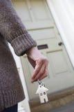 Vrouw die zich buiten de Nieuwe Sleutel van de Holding van het Huis bevindt stock afbeelding