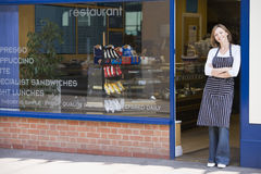 Vrouw die zich in deuropening van restaurant het glimlachen bevindt royalty-vrije stock afbeelding