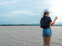 Vrouw die zich dichtbij de rivier en speltelefoon bevinden Royalty-vrije Stock Foto's