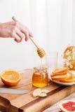 Vrouw die zich dichtbij lijst met citrusvruchten bevinden en honing houden Royalty-vrije Stock Fotografie