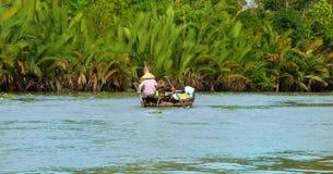 Vrouw die zich door boot, het gemeenschappelijkste vervoersgemiddelde bewegen van landelijke mensen in Mekong delta te roeien Royalty-vrije Stock Afbeelding