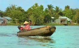 Vrouw die zich door boot, het gemeenschappelijkste vervoersgemiddelde bewegen van landelijke mensen in Mekong delta te roeien Royalty-vrije Stock Fotografie