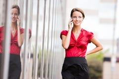 Vrouw die zich door een bouw en gebruikende celtelefoon bevindt Stock Fotografie