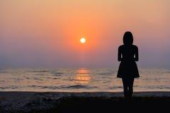 Vrouw die zich door het overzees en de zonsondergang bevinden stock afbeelding