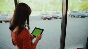 Vrouw die zich door het venster en het werk aangaande tablet bevinden Het groene scherm stock videobeelden