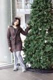 Vrouw die zich door Kerstmisboom op overeenkomstcentrum bevindt stock afbeeldingen