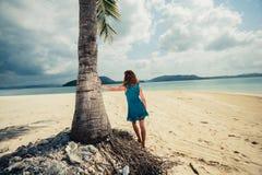Vrouw die zich door palm op tropisch strand bevinden Stock Afbeeldingen