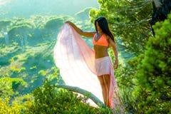 Vrouw die zich in een bos met bomen op de achtergrond bevinden stock fotografie