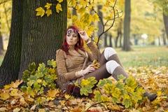 Vrouw die zich in een park in de herfst bevindt Stock Foto's