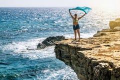Vrouw die zich met het golven in de wind met een zakdoek op Th bevinden Stock Fotografie