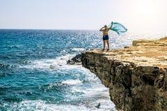 Vrouw die zich met het golven in de wind met een zakdoek op Th bevinden Royalty-vrije Stock Fotografie